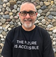Photo of Mike Marotta standing in front of a rock wall with the words The Future is Accessible on his shirt